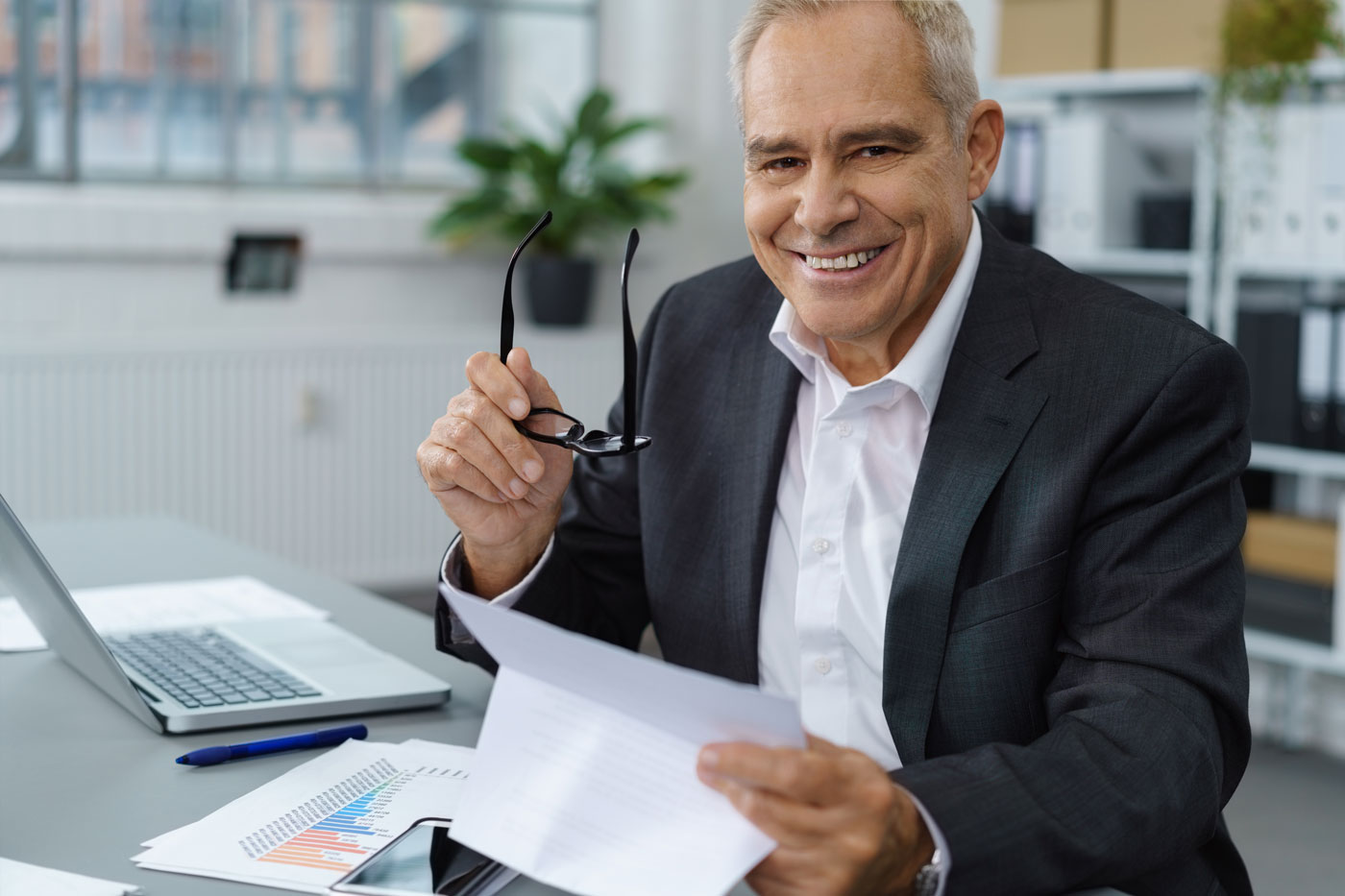 Men in office smiling with glasses in hands